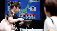 Des piétons passent devant un écran de télévision diffusant des informations sur l'exécution de six membres de la secte Aum Vérité Suprême, le 26 juillet 2018 à Tokyo [Behrouz MEHRI / AFP]