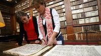 """Elisabeth Perié, responsable des bibliothèques d'Ajaccio, et Vannina Schirinsky-Schikhmatoff, conservatrice, admirent le """"Thesaurum Hyeroglyphicorum"""", premier livre d'égyptologie, dans la bibliothèque d'Ajaccio, le 18 avril 2018 [PASCAL POCHARD-CASABIANCA / AFP]"""