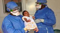 La petite Noubia dans les bras d'une soignante le 28 novembre 2015 à Conakry quelques jours après avoir été déclarée guérie du virus Ebola [CELLOU BINANI / AFP]