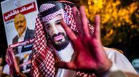 Un manifestant, les mains rougies et portant un masque à l'effigie du prince héritier saoudien Mohammed Ben Salmane, près d'une photo du  journaliste Jamal Kashoggi lors d'une manifestation devant le consulat saoudien à Istanbul, le 25 octobre 2018 [Yasin AKGUL / AFP]