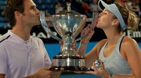 Les Suisses Roger Federer et Belinda Bencic embrassent le trophée après avoir remporté la Hopman Cup, le 6 janvier 2018 à Perth [TONY ASHBY / AFP/Archives]