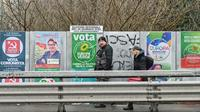 Des passants marchent devant des panneaux électoraux le 19 janvier 2020 à Bologne, avant les élections régionales en Emilie-Romagne (Italie) [ANDREAS SOLARO / AFP]