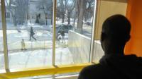 Un réfugié de Djibouti regarde par la fenêtre du conseil œcuménique de l'immigration au Manitoba, au Canada, le 9 février 2017  [Julien BESSET / AFP]