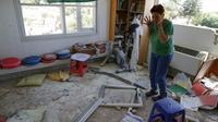 Une femme au milieu des dégâts provoqués par l'explosion d'une roquette tirée de la bande de Gaza et qui s'est abattue sur le village de Netiv Haasara en Israël, le 4 mai 2019  [Jack GUEZ  / AFP]