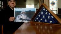 Miguel Perez montre la photo de son fils Miguel Perez Jr. aux côtés du drapeau américain le 4 avril 2017 à Chicago [Joshua LOTT / AFP]