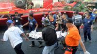 Des urgentistes transportent le corps d'une personne tuée dans la chute d'un bus, le 16 décembre 2013 à Manille [Jay Directo / AFP]