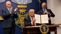 Le président américain Donald Trump signe un décret lors de la cérémonie d'investiture du secrétaire américain à la Défense James Mattis (d) en présence du vice-président Mike Pence (g), le 27 janvier 2017 au Pentagone, à Washington [MANDEL NGAN / AFP]