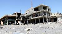 Des habitants inspectent des bâtiments endommagés par les raids nocturnes  du régime dans la ville de Nawa, dans la province de Deraa, le 18 juillet 2018 [Ahmad al-Msalam / AFP]