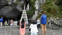 Des pèlerins prient le 15 août 2017 devant la grotte de Massabielle à Lourdes, où Bernadette Soubirous dit avoir vu des apparitions de la Vierge Marie [PASCAL PAVANI / AFP/Archives]