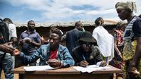 Des hommes s'inscrivent pour participer à un vote symbolique à Béni, en RDCongo,  le 30 décembre 2018. Cette région est privée d'élections en raison de problèmes de sécurité et de la maladie d'Ebola [ALEXIS HUGUET / AFP]
