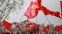 Des Chinois agitent des drapeaux et entonnent des chants patriotiques lors de la commémoration des 70 ans de la République populaire de Chine, le 18 avril 2019 [STR / AFP]