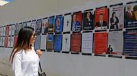 Une Tunisienne passe devant des affiches de campagne des candidats à la présidentielle, le 7 septembre 2019 à Tunis [FETHI BELAID / AFP/Archives]