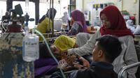 Un rescapé du tsunami entouré de sa famille dans un hôpital à Kalianda en Indonésie le 25 décembre 2018 [MOHD RASFAN / AFP]
