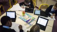 Des élèves étudient avec des tablettes numériques en France [Fred Dufour / AFP/Archives]