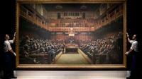 """Deux assistants manipulent la toile de Banksy """"Devolved Parliament"""" (Parlement dévolu), le 27 septembre 2019 à Londres [Tolga Akmen / AFP]"""
