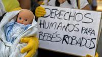 """Des manifestants arborent un poupon et une pancarte réclamant des """"droits"""" pour """"les bébés volés"""" sous la dictature de Franco, à Madrid le 26 juin 2018 [OSCAR DEL POZO / AFP/Archives]"""