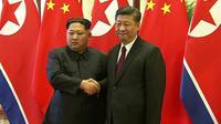 Le président chinois Xi Jinping et le dirigeant nord-coréen Kim Jong Un, sur des images diffusées par la télévision chinoise le 28 mars 2018 concernant leur rencontre à Pékin. Il s'agit du premier voyage à l'étranger de Kim Jong Un. [ / AFP]