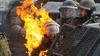 Une policière atteinte par un cocktail molotov pendant une manifestation à Santiago du Chili, le 4 novembre 2019 [CLAUDIO REYES / AFP]