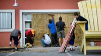 Des habitants de Panama City, en Floride, protègent la vitrine d'une pizzeria à l'approche de l'ouragan Michael, le 9 octobre 2018 [Brendan Smialowski / AFP]