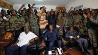 Une délégation de soldats rebelles se tiennent derrière le ministre ivoirien de la Défense Alain Richard Donwahi (C) après des négociations, le 7 janvier 2017 à Bouaké   [SIA KAMBOU / AFP]