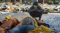 Un survivant du tsunami devant le corps de sa femme retrouvé parmi des dépouilles, le 2 octobre 2018 à Palu, ville indonésienne frappée par un séisme et un tsunami [BAY ISMOYO / AFP]