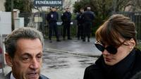 L'ancien président Nicolas Sarkozy (G) et Carla Bruni-Sarkozy parlent aux journalistes devant le funérarium du Mont-Valérien, où repose la dépouille de Johnny Hallyday, le 8 décembre 2017 à Nanterre, près de Paris [Martin BUREAU / AFP]