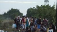Une famille de migrants passent la frontière le 24 août 2015 entre la Serbie et la Hongrie près du village de Asotthalom, après que les fils barbelés ont été coupés [CSABA SEGESVARI / AFP]