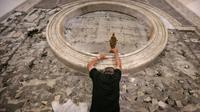 Soutenu à bout de bras, le cardinal Philippe Barbarin escalade le mur de l'église du Saint-Esprit pour y déposer une statue de la Vierge, à Mossoul le 25 juillet 2017 [SAFIN HAMED / AFP]