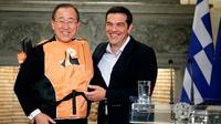 """Le secrétaire général de l'ONU Ban Ki-moon (g) en gilet de sauvetage offert par le Premier ministre grec Alexis Tsipras (d) comme un  """"symbole"""" des traversées périlleuses des migrants, le 18 juin à Athènes [Yorgos KONTARINIS / Eurokinissi/AFP]"""