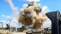 Photo prise le 12 avril 2019 montrant une colonne de fumée s'élever derrière des chars des forces loyales au Gouvernement d'union nationale (GNA) à Wadi Rabi, à quelque 30 km au sud de la capitale libyenne [Mahmud TURKIA / AFP]
