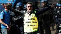 """Un militant porte une pancarte avec l'inscription """"Macron, notre drame français"""" en référence à l'incendie qui a dévasté Notre-Dame de Paris, le 20 avril 2019 [Zakaria ABDELKAFI / AFP]"""