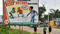 Une affiche de la Commission électorale indépendante, dans les rues d'Abidjan, le 17 décembre 2016 [Sia KAMBOU / AFP]