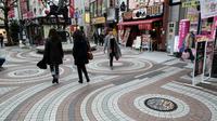 Des piétons passent à côté de plaques d'égout décorées, le 22 novembre 2017 à Kawaguchi, au Japon [Behrouz MEHRI / AFP]