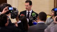 Photo fournie le 18 décembre 2017 par l'agence officielle SANA du président syrien Bachar Al-Assad parlant à des journalistes à Damas [HO / SANA/AFP]