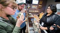 Des touristes venus de d'Arizona sentent des têtes de cannabis dans un magasin de Desert Hot Springs, en Californie, le 1er janvier 2018. [Robyn Beck / AFP]