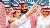 Le prince héritier d'Arabie saoudite Mohammed ben Salmane pose pour une photo avec un participant du forum Future Investment Initiative (FII) à Ryad, le 23 octobre 2018. [Bandar AL-JALOUD / Saudi Royal Palace/AFP]