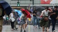 Les passants à Tokyo se protègent de la pluie provoquée par le typhon Jongdari, le 28 juillet 2018 [Jiji Press / JIJI PRESS/AFP]