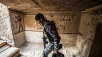 Un membre des forces de sécurité égyptiennes à l'entrée d'une tombe datant de 2.000 ans dévoilée le 5 avril 2019 à Akhmim [Khaled DESOUKI / AFP]