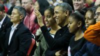 Barack Obama entouré par ses filles Malia (g) et Sasha (d), lors d'un match de basket dans le Maryland, le 17 novembre 2013 [Drew Angerer / Getty Images/AFP/Archives]