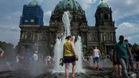 Des visiteurs se rafraïchissent dans la fontaine de la cathédrale de Berlin, le 4 août 2018 [John MACDOUGALL / AFP]