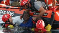 Les membres de l'ONG Proactiva repâchent une femme en Méditerranée à à environ 80 milles nautiques au nord-est de Tripoli le 17 juillet 2018 [PAU BARRENA / AFP]