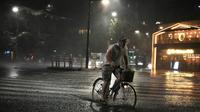 Un homme se déplace à vélo dans Tokyo, la capitale japonaise frappée par le typhon Faxai le 9 septembre 2019 [Charly TRIBALLEAU / AFP]