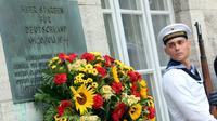 Un soldat allemand près d'une plaque à la mémoire des officiers fusillés pour leur implication dans l'attentat contre Hitler en 1944, au mémorial de la résistance allemande à Berlin le 20 juillet 2014 [WOLFGANG KUMM / DPA/AFP/Archives]