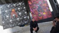 Un homme pose devant des oeuvres de l'artiste britannique de rue Banksy, le 18 octobre 2013 à New York  [Michael Loccisano / Getty/AFP/Archives]