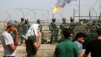 Des jeunes irakiens manifestent devant l'entrée d'un champ pétrolier gardé par des soldats, le 14 juillet 2018 à Al-Qournah, dans la province de Bassora (sud) [Haidar MOHAMMED ALI / AFP]