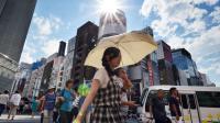 Des piétons utilisent des parapluies pour se protéger du soleil, le 11 juillet 2014 à Tokyo [Yoshikazu Tsuno / AFP]