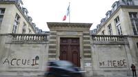 """Des militants d'associations de défense des migrants ont tagué """"accueil de merde"""" sur la façade du ministère du Logement à Paris le 16 décembre 2017 pour dénoncer les conditions de réception des migrants en France [Thomas SAMSON / AFP]"""