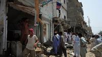 Des Pakistants viennent constater les dégats causés par une explosion, le 11 mai 2013 à Karachi [Asif Hassan / AFP/Archives]