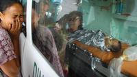 Une mère pleure son enfant pris en charge par une ambulance dans le village de Lampahan en Indonésie, le 2 juillet 2013 [Reza Juanda / AFP]