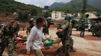 Des sauveteurs transportent une victime du séisme dans le district de Ludian de la province chinoise du Yunnan, le 4 août 2014 [ / AFP]